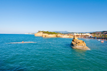 Famous Sidary beach, people sunbath on the shore. Corfu, Greece.