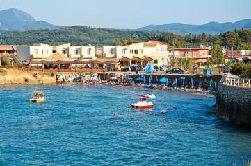 Sidary resort, people sunbath on the sandy beach. Corfu, Greece.