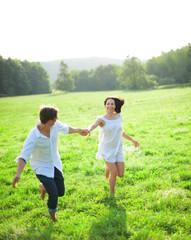 Junges Paar läuft barfuß über Wiese