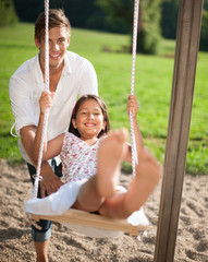 Vater schaukelt seine Tochter auf dem Spielplatz
