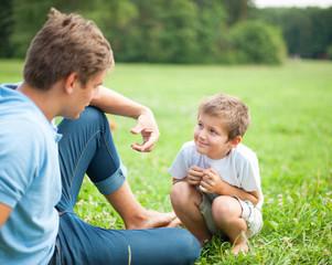 Vater und Sohn unterhalten sich im park
