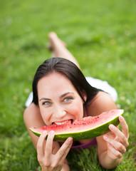 Junge Frau isst saftige Wassermelone