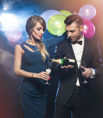 Couple celebrating new year's eve wth champagne