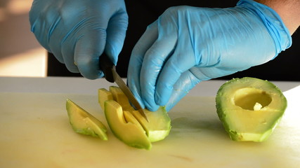 Professional chef hands cutting an avocado sliced