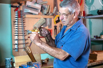 man working carving wood with a chisel and hammer