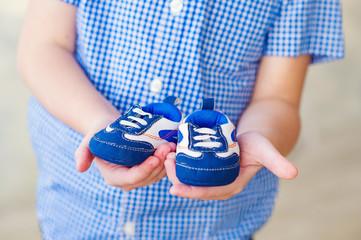 Closeup kid hands holding baby booties