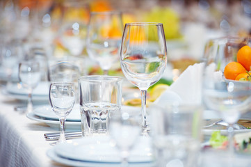 Big celebratory served table with glasses and plates
