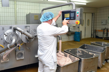 Arbeiter bedient Maschine mit Wurstmasse