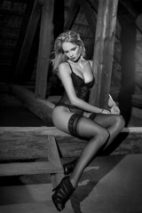 Sensual woman in underwear sit on timber black and white