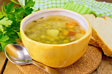 Soup of green peas in yellow bowl with bread on board