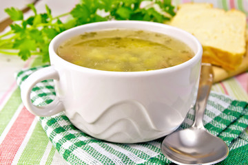 Soup of green peas with bread on tablecloth