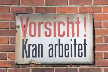 Vorsicht Kran arbeitet retro sign on brick wall