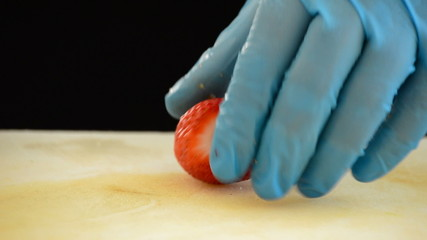 Professional chef hands cutting a strawberry in small cubes
