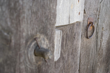 Old run-down wooden door and wooden lock out of focus