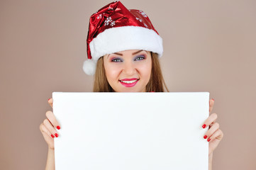 Beautiful christmas woman in santa hat with blank white board
