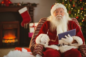 Smiling santa holding glasses and tablet