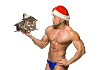 Attractive young muscle man smiling in Santa Claus's red hat