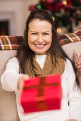Pretty brunette woman offering christmas gift