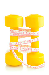 two yellow dumbbells and tape measure placed vertically isolated