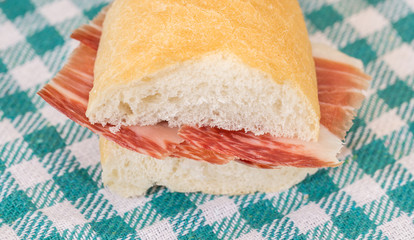 Front view of Serrano ham sandwich over checkered tablecloth