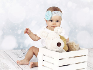 Little baby girl sitting on the floor with box of plush toys
