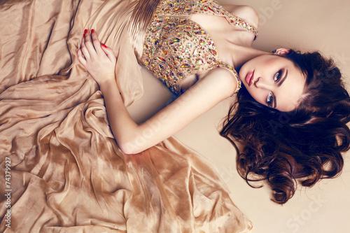 Fototapeta beautiful brunette in luxurious sequin dress posing at studio