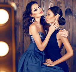 two beautiful women with dark hair in luxurious dresses