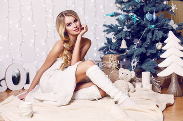 beautiful blond girl posing beside a Christmas tree