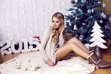 beautiful girl with blond hair posing beside a Christmas tree