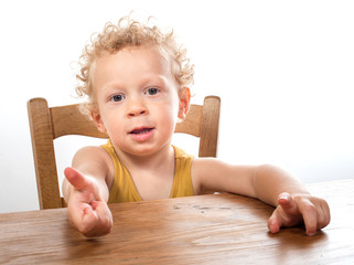 little blonde child sitting at table