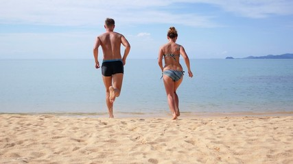 Happy Couple Running in Sea on Beach. Slow Motion.