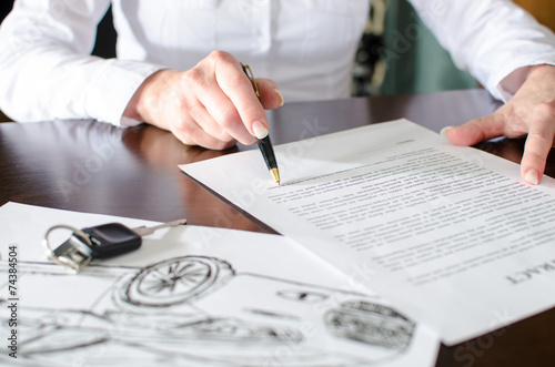 Woman reading a car purchase contract - 74384504