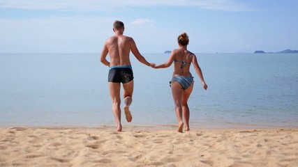 Love Couple Running into Sea Water at Beach. Slow Motion.