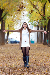Beautiful girl having fun in the autumn.