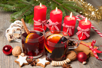 Red mulled wine on table with burning candles