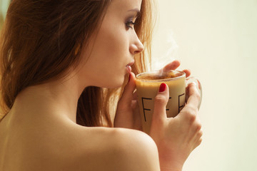 girl standing at the window with a hot Cup coffee