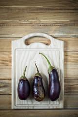 Three ripe eggplant on a chopping board