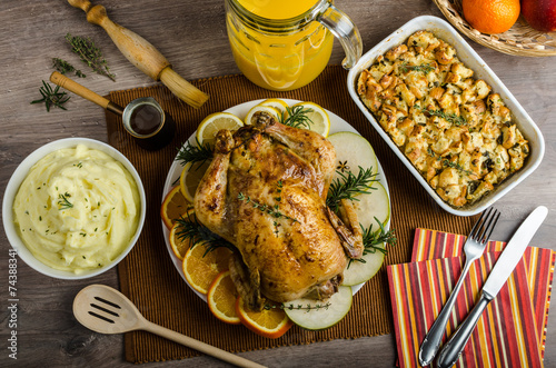 Fototapeta Feasting - stuffed roast chicken with herbs