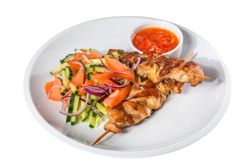 Skewers with vegetables and sauce on the white plate