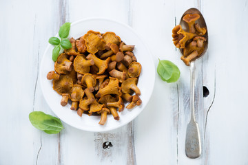 Above view of marinated chanterelles with green basil leaves