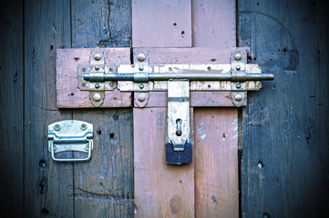 Retro vintage style picture of wooden door with lock.