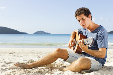 Young men playing guitar on the beach