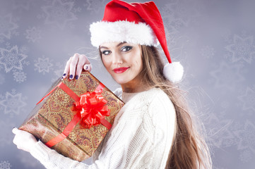 Santa girl with gift box isolated against a snowy background.