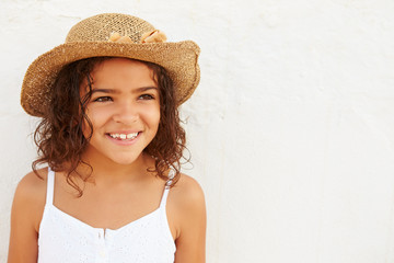 Smiling Young Girl Wearing Hat Standing Against White Wall