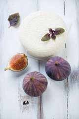Close-up of round cheese and fig fruits, white wooden surface
