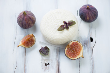 Round cheese with fig fruits over white rustic wooden background