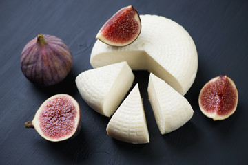 Close-up of sliced round cheese and fig fruits, horizontal shot