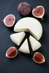 Sliced cheese and figs, black wooden background, high angle view