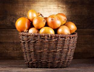 fresh onions in wicker basket