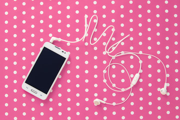 Small headphones with mobile phone on pink vintage paper with do